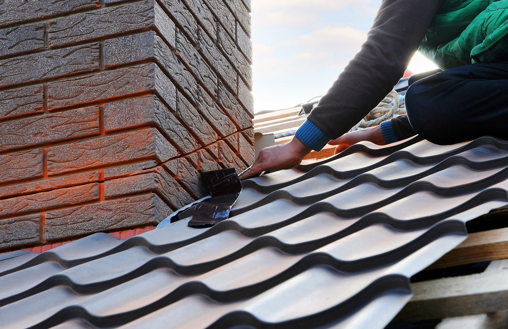 Roofer builder worker attach metal sheet to the chimney. Unfinis