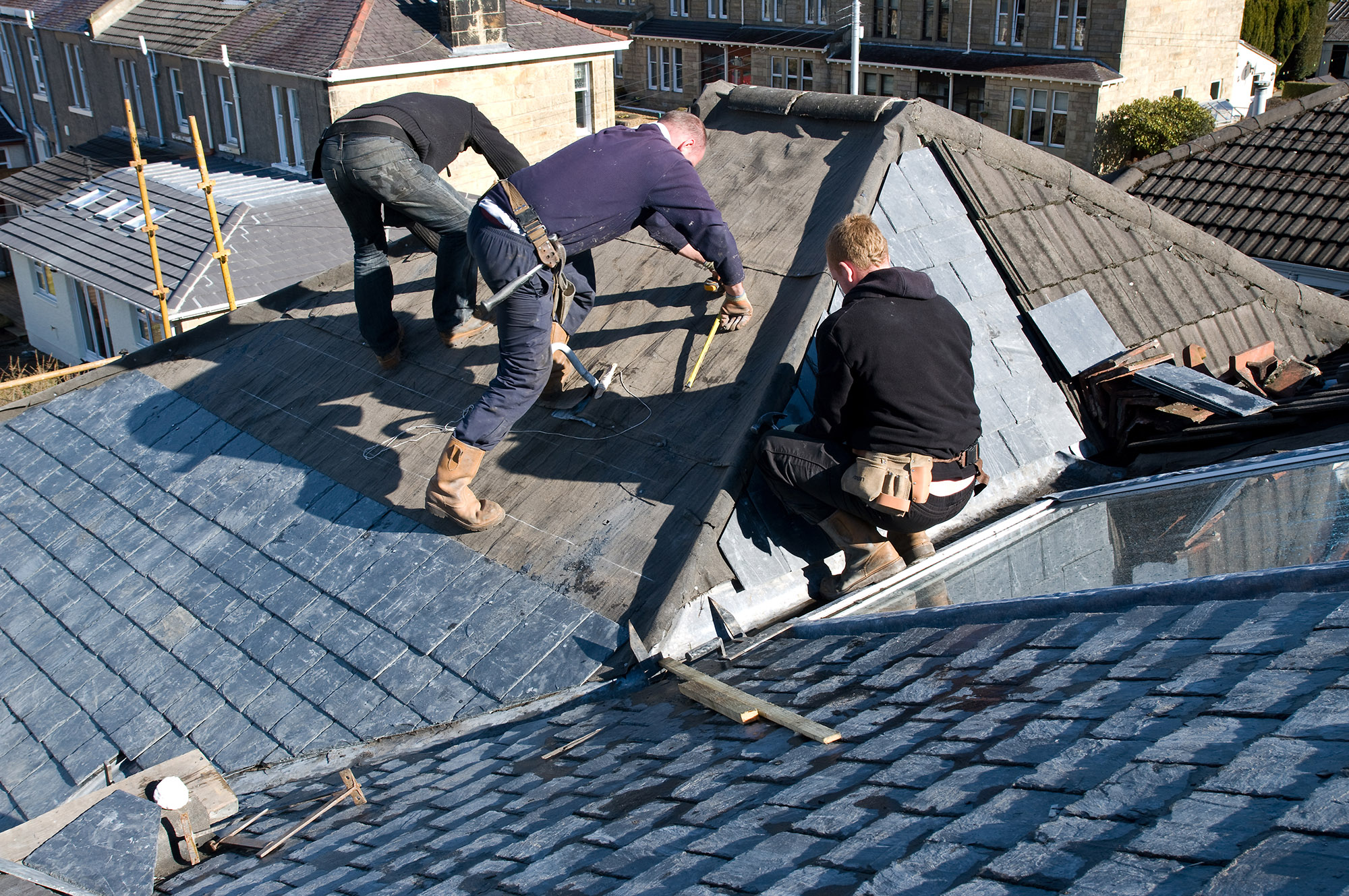 Roofers replacing roof on home with slate tiles