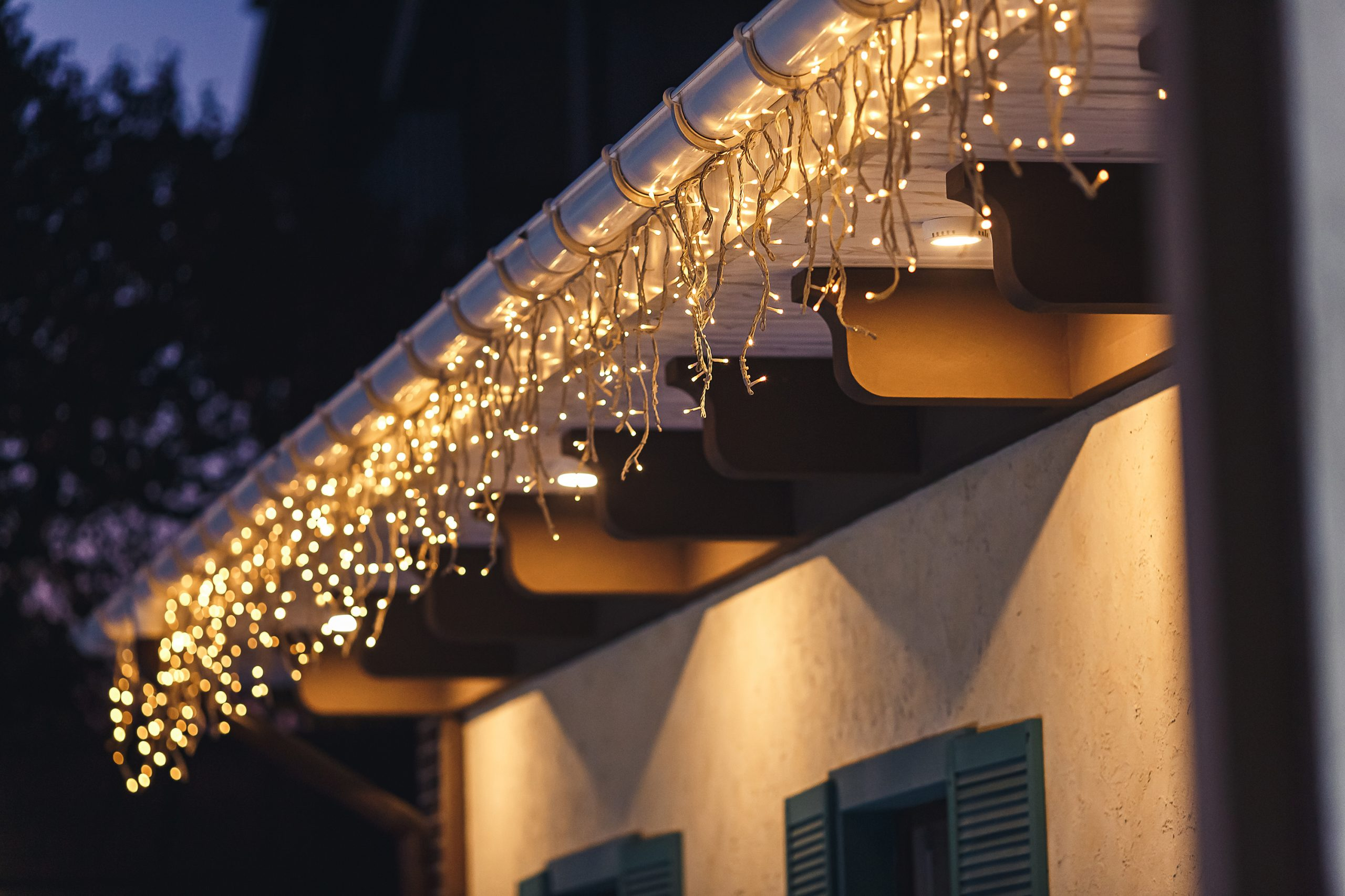 a garland hangs from the roof at night and illuminates the facade of the building.